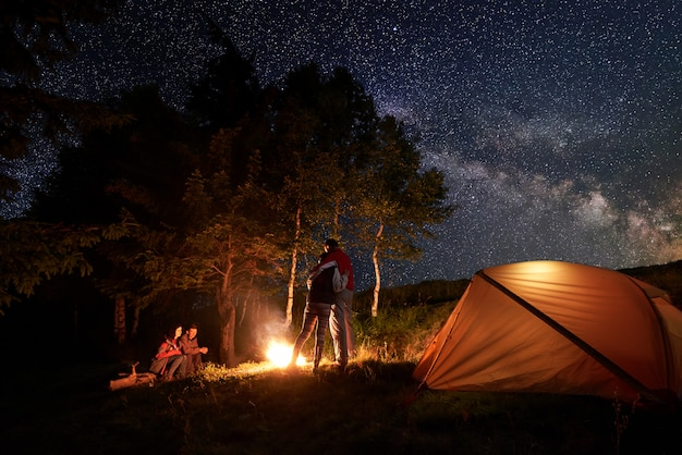 Turyści podczas nocy na kempingu przy ognisku w pobliżu pomarańczowego namiotu. jedna para się tuli, druga siedzi na pniu pod gwiaździstym niebem i drogą mleczną na tle drzew