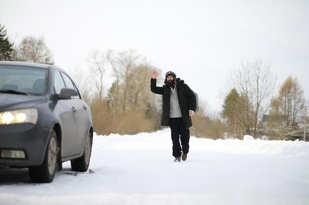 Turyści podróżują przez zaśnieżony kraj. po drodze spacer i autostop.