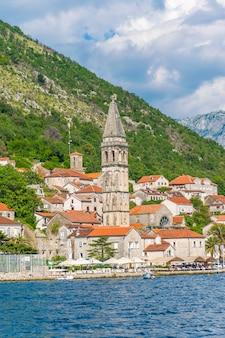 Turyści popłynęli na jachcie obok miasta perast w zatoce boka w kotorze.
