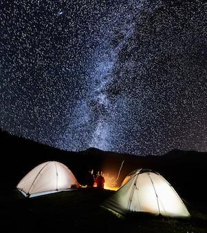 Turyści przy ognisku w pobliżu namiotu w nocy