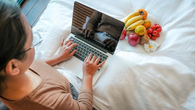 Turyści ręcznie używali laptopa i jedzą owoce na łóżku w luksusowym pokoju hotelowym koncepcja zdrowej żywności