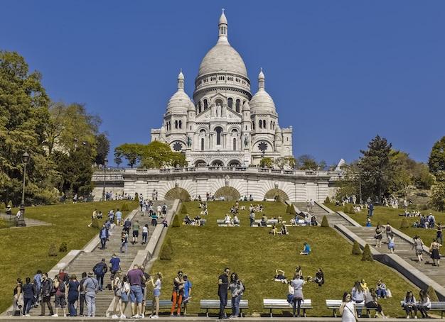 Turyści są fotografowani przed wzgórzem świątyni sacre coeur paris france