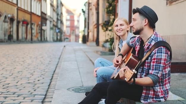 Turyści siedzący na chodniku, grający na gitarze i odpoczywający