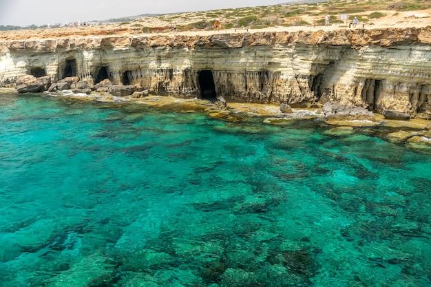 Turyści spacerują wzdłuż wybrzeża w pobliżu malowniczych morskich jaskiń
