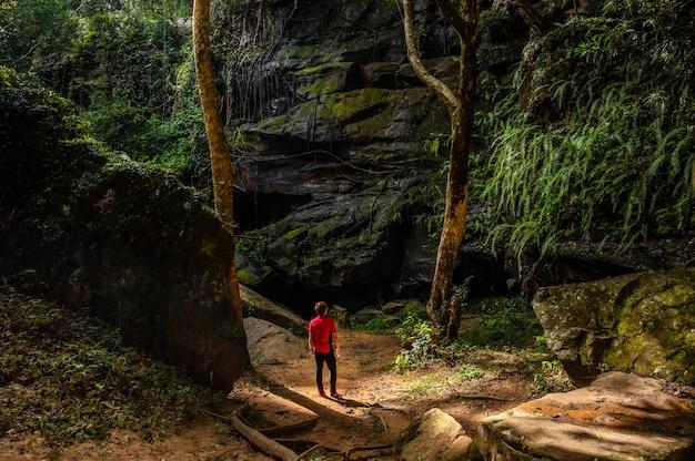 Turyści stoją przed dużą skałą przy wodospadzie tat fa w parku narodowym phu wiang tajlandia