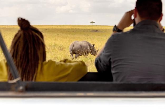 Turyści w safari samochodowym patrzejący nosorożec w afrykańskiej sawannie. park narodowy masai mara, kenia.