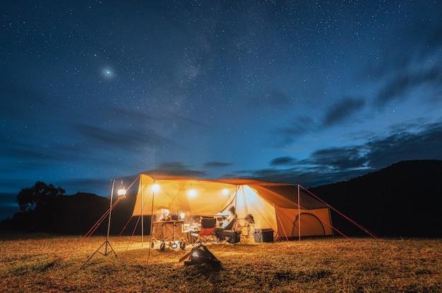 Turyści w żółtym namiocie na wzgórzu z drogą mleczną na nocnym niebie w parku narodowym