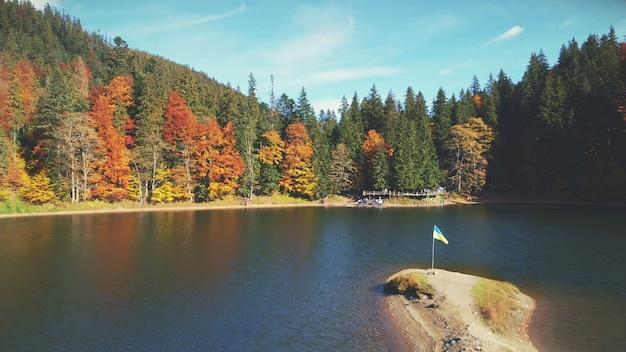 Turyści wędrują wzdłuż piaszczystego brzegu jeziora przez lasy mieszane
