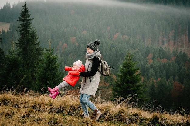 Turyści z plecakiem podróżnym na mglistym szczycie wysokich skał. szczęśliwa rodzina mama trzyma i skręca córkę, ciesząc się razem, stań na szczycie góry.