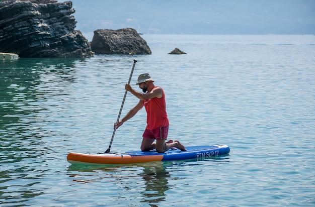 Turyści zajmują się wiosłowaniem na pokładzie (sup) na powierzchni spokojnego morza.