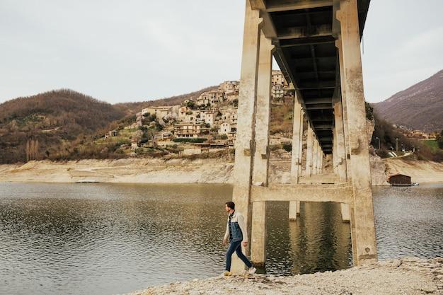 Turysta chodzenie po kamieniach pod dużym mostem ze wzgórzami i wioską, przyroda