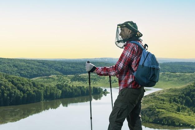 Turysta człowiek w górach jesienią. szczęśliwy podróżnik z moskitierami podczas pieszej wycieczki. ochrona przed owadami ssącymi krew.