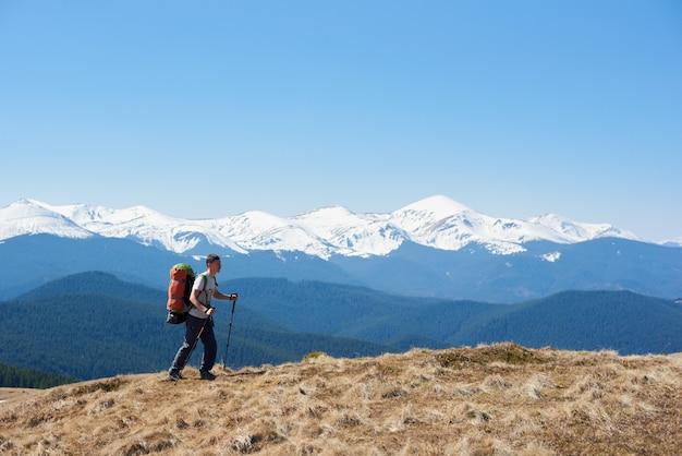 Turysta człowiek z plecakiem, podziwiając widok spacery na szczycie góry za pomocą laski turystyczne