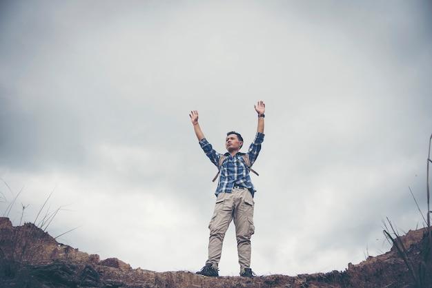 Turysta doping raduje się i raduje z podniesionymi na niebie ramionami po wędrówce.