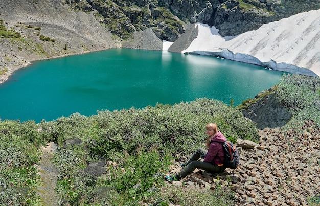Turysta dziewczyna z plecakiem siedzi na skałach w górach w pobliżu błękitnego jeziora. rosja ałtaj