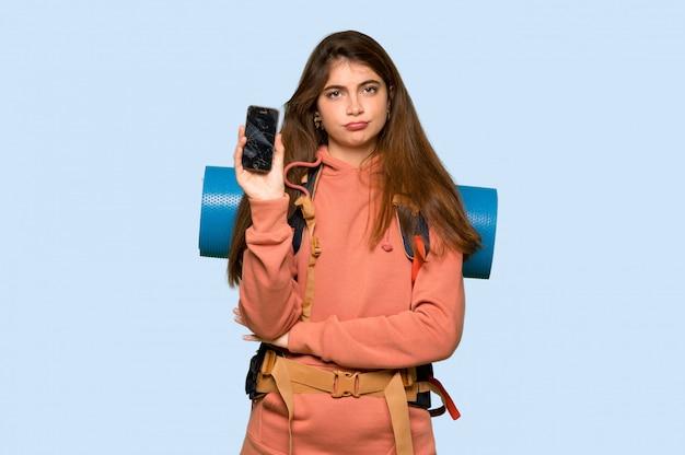 Turysta dziewczyna ze zepsutym telefonem na niebiesko