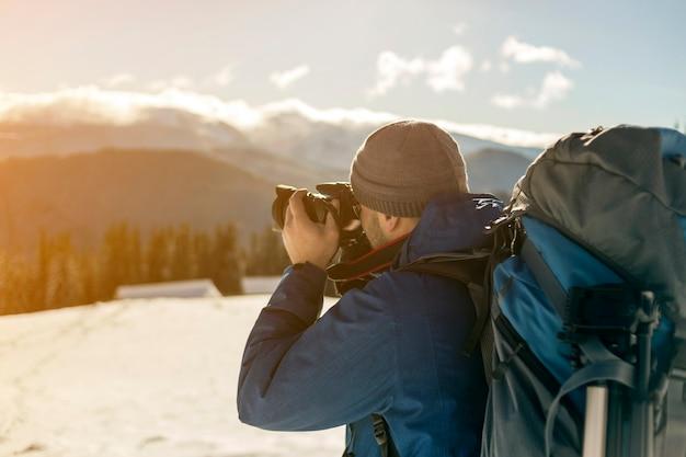Turysta fotograf turystyczny mężczyzna w ciepłej odzieży z plecakiem i aparatem biorącym obraz śnieżnej doliny i drzewiastych szczytów górskich krajobraz pod błękitnym niebem w słoneczny zimowy zimny dzień.
