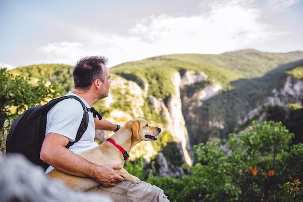 Turysta i jego pies siedzi na szczycie góry