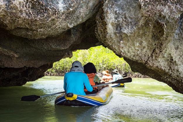 Turysta i żeglarz przepływa kajakiem przez formacje krasowe tham lod, aby odwiedzić lagunę i bagno lasów namorzynowych w zatoce phang nga w tajlandii.