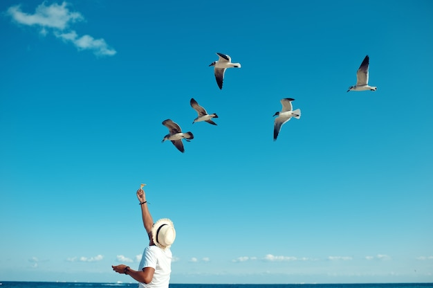 Turysta karmiący stado mew na plaży playa del carmen w meksyku