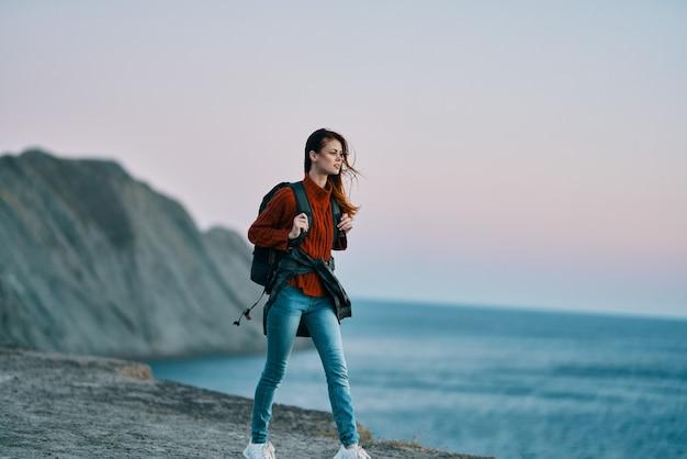 Turysta kobieta podróżuje po górach w przyrodzie z plecakiem na plecach czerwony sweter rock