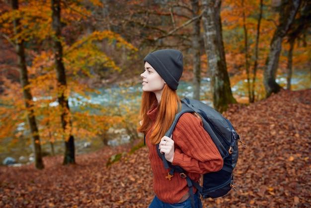 Turysta kobieta spacery po lesie jesienią w przyrodzie w pobliżu rzeki i liści krajobraz