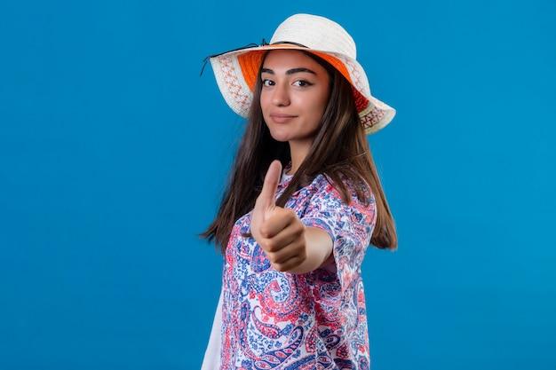 Turysta kobieta z kapeluszem pozytywny i szczęśliwy uśmiechnięty pokazując kciuki do góry stojąc na niebiesko