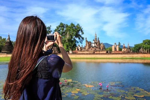 Turysta kobieta zrobić zdjęcie w historycznym parku sukhothai