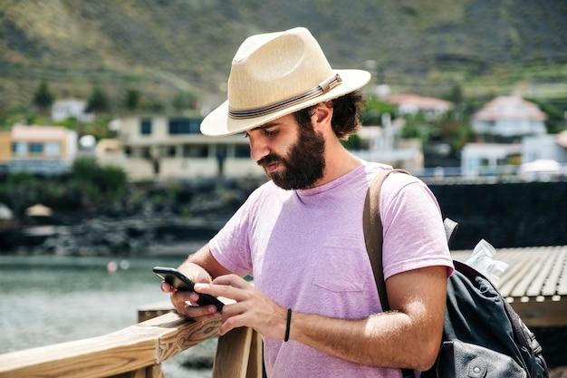 Turysta korzysta z telefonu komórkowego w nadmorskiej miejscowości el hierro na wyspach kanaryjskich