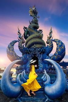Turysta ma na sobie żółtą sukienkę i stoi przy niebieskim posągu w chiang rai w tajlandii