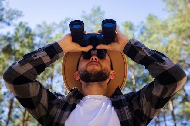 Turysta mężczyzn w kapeluszu i szarej kraciastej koszuli patrzy przez lornetkę na tle lasu.