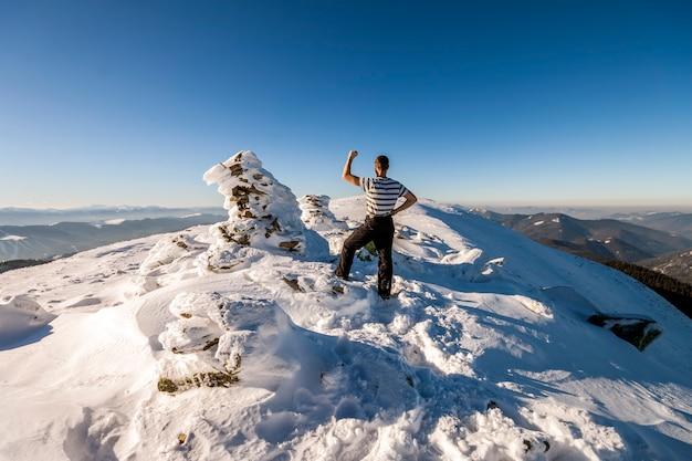 Turysta mężczyzna na szczycie góry w zimie