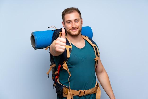 Turysta mężczyzna nad niebieską ścianą z kciukami do góry, ponieważ stało się coś dobrego