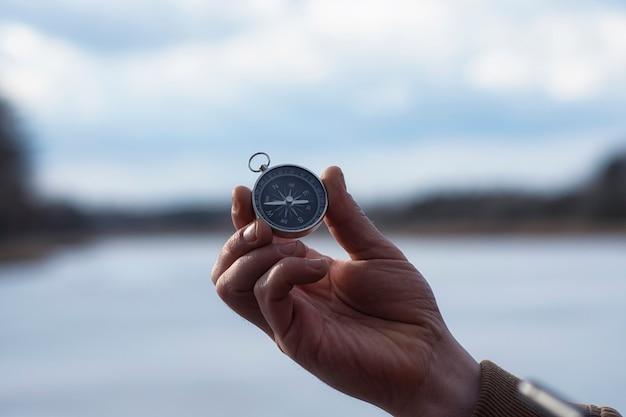 Turysta mężczyzna trzyma w ręku zbliżenie kompasu morskiego na tle jeziora.