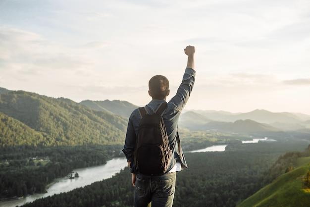 Turysta mężczyzna z plecakiem z podniesioną ręką na szczycie góry.