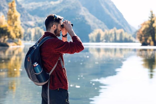 Turysta młody człowiek podróżnik z plecakiem patrząc na krajobraz z lornetką w jeziorze.