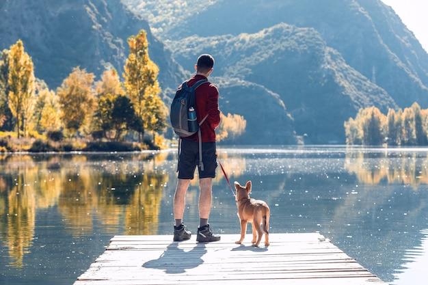 Turysta młody człowiek podróżnik z plecakiem z psem patrząc na krajobraz w jeziorze.