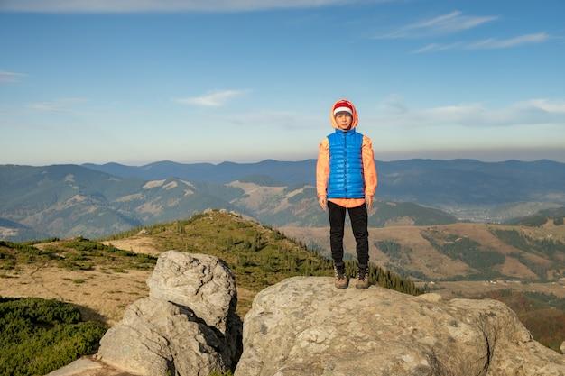 Turysta młody dziecko chłopiec stojący w górach, ciesząc się widokiem niesamowitego górskiego krajobrazu.