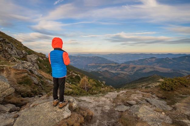 Turysta młody dziecko chłopiec stojący w górach z widokiem na niesamowity krajobraz górski.