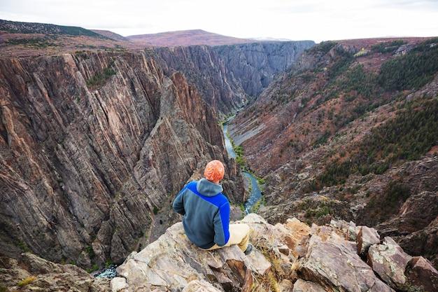Turysta na granitowych klifach czarnego kanionu gunnison, kolorado, usa
