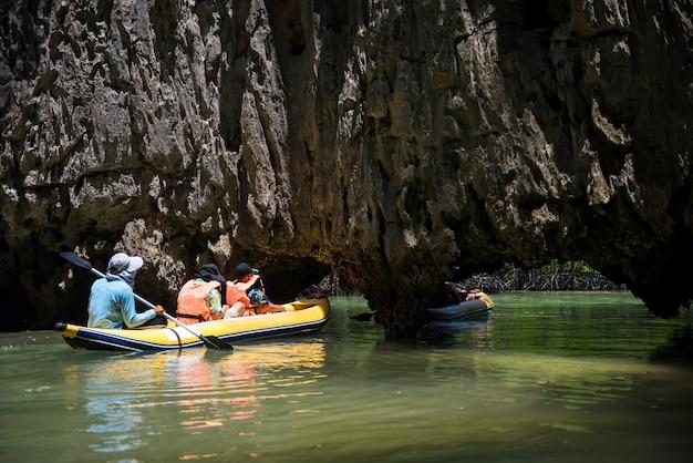 Turysta na kajaku spływającym przez tham lod (mała jaskinia grota) formacji kras, aby odwiedzić bagno dżungli w lagunie i drzewie namorzynowym w zatoce phang nga, tajlandia.