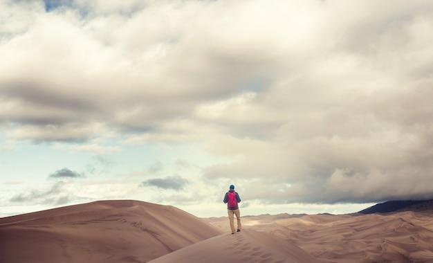 Turysta na piaszczystej pustyni. czas wschodu słońca.