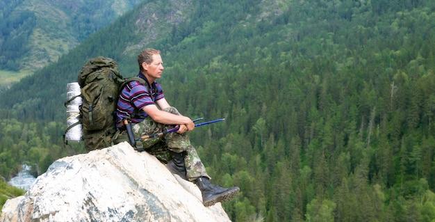 Turysta na wysokiej górze patrzy na przyrodę.