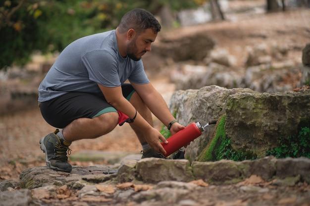 Turysta napełnia swoją ekologiczną aluminiową butelkę na wodę z naturalnego źródła