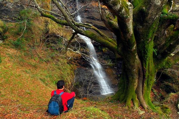 Turysta obserwuje wodospad uguna. park przyrody gorbeia. kraj basków. hiszpania
