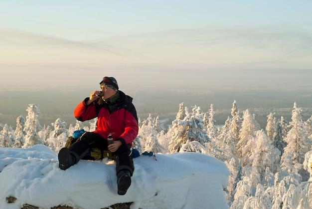Turysta odpoczywa na szczycie ośnieżonej skały nad zimowym lasem i pije herbatę z termosu