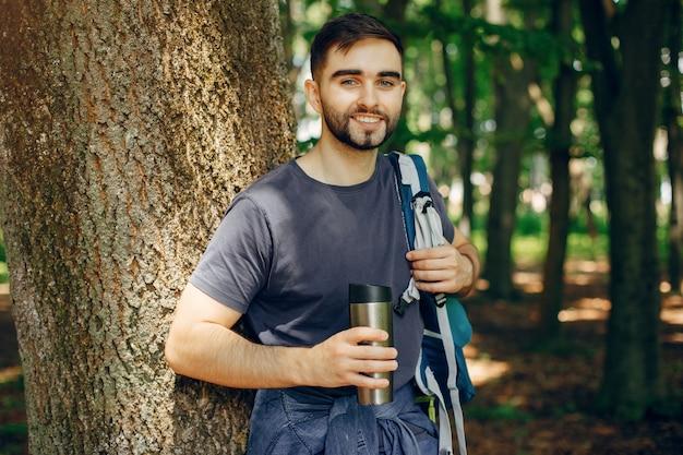 Turysta odpoczywa w letnim lesie