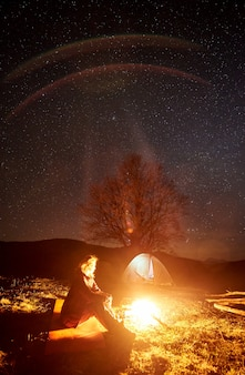 Turysta odpoczywa w pobliżu ogniska pod rozgwieżdżonym niebem