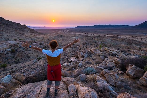 Turysta ogląda oszałamiająco widok jałowa dolina w namib pustyni, namibia, afryka