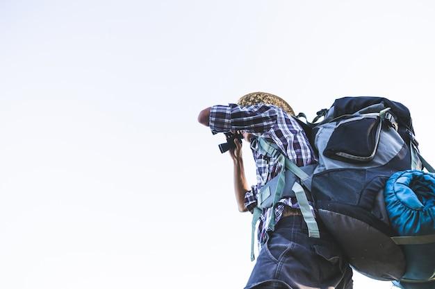 Turysta ogląda przez lornetek na pogodnym chmurnym niebie od góra wierzchołka.